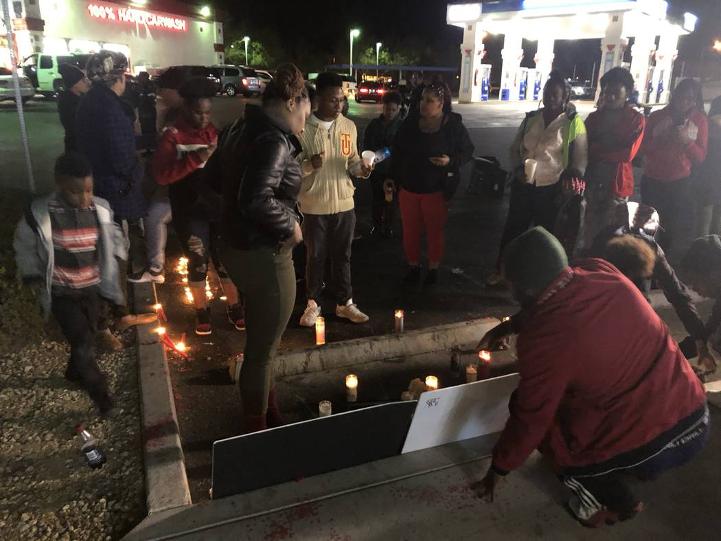 Sydney Harris, 33, stands closest to the front of posters remembering her son, 16-year-old LaMadre Harris, after a vigil on Wednesday night. The 16-year-old boy died after a shooting in North Las ...