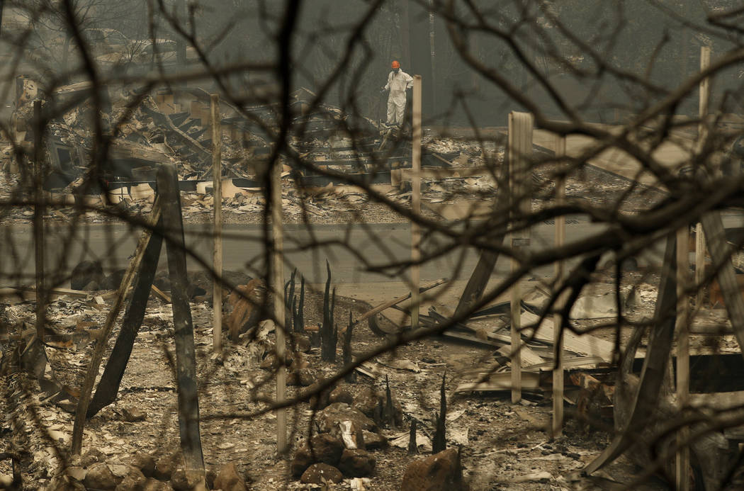 A search and rescue worker searches for human remains at a burned out trailer park from the Camp Fire, Tuesday, Nov. 13, 2018, in Paradise, Calif. The deadliest, most destructive blaze in Californ ...