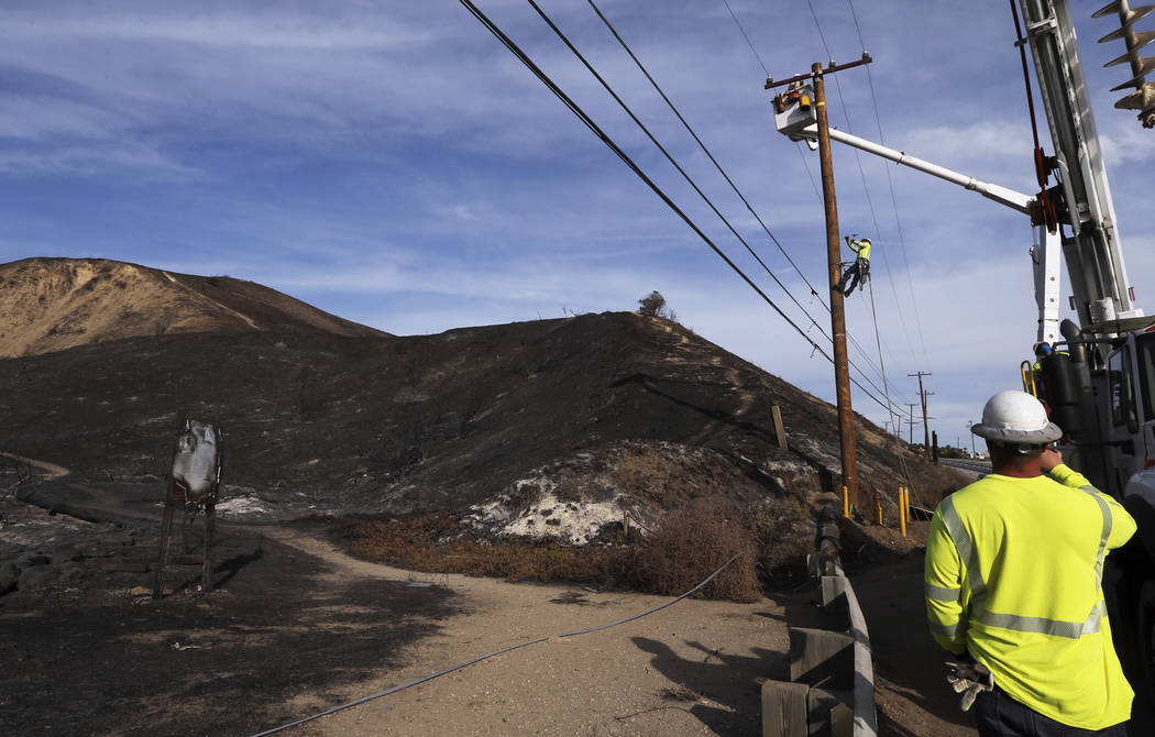 Southern California Edison crews work to replace burned power poles and lines destroyed by the Woolsey Fire over a burned-over hillside along Pacific Coast Highway in Malibu, southern California, ...