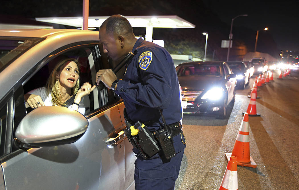 California Highway patrol Officer S. Kizito verifies that a woman seeking to return to Malibu in Southern California is an actual resident after Woolsey Fire evacuation orders were lifted for the ...