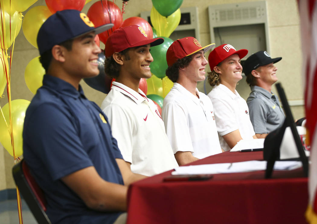 Desert Oasis baseball players, from left, Aaron Roberts, DJ Jefferson, Campbell Holt, Josh Sharman and Parker Schmidt pose in their new college hats during signing day at Desert Oasis High School ...
