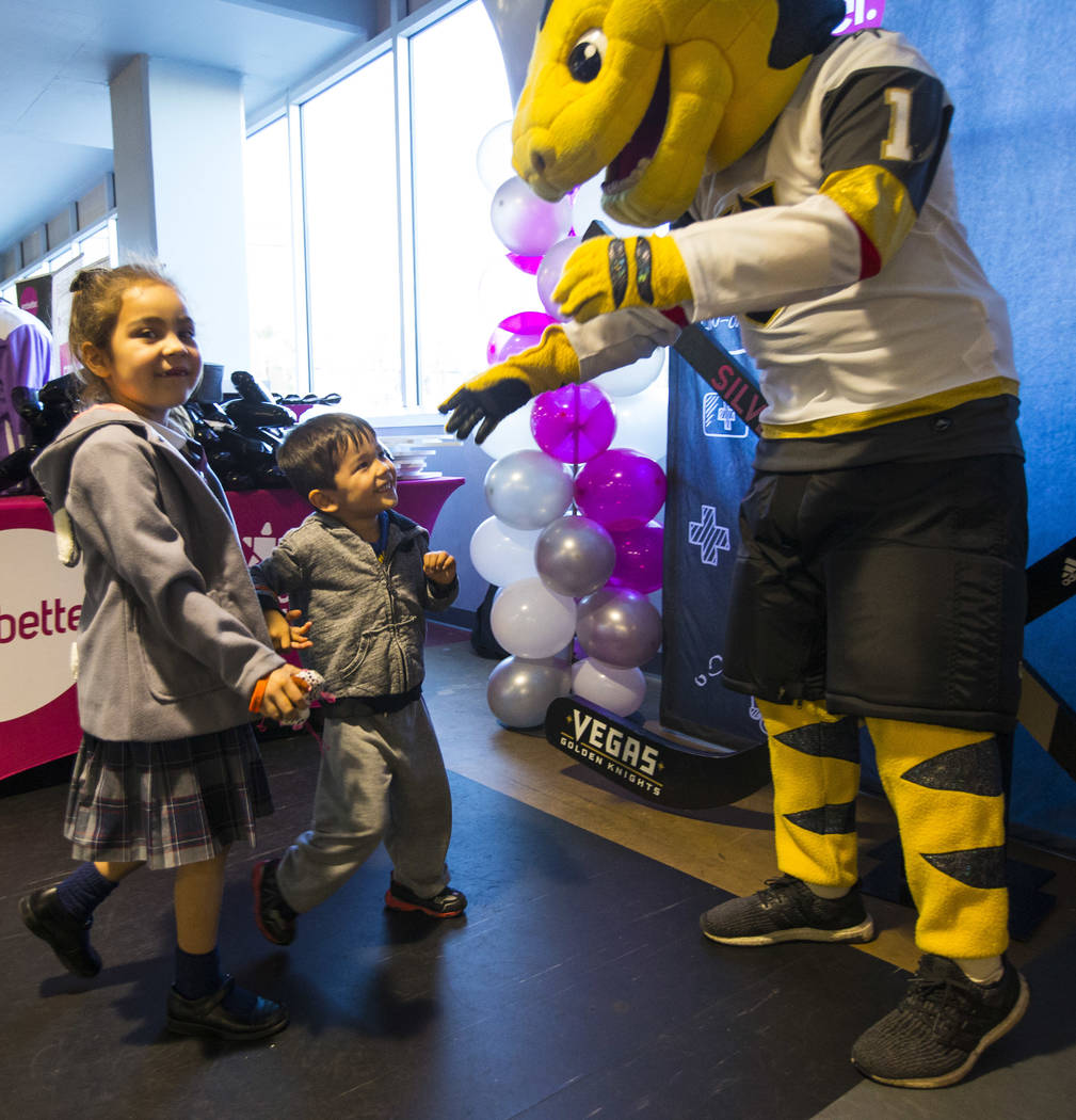 "Bailey Detmer, 5, with her brother Michael, 3, greet Golden Knights mascot Chance during the second annual ""Silver and Gold"" food drive at City National Arena in Las Vegas on Thursday, N ..."