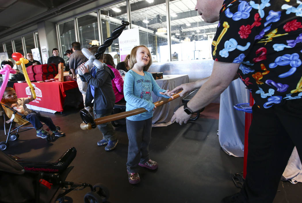 "Balloon artist Roger Goodin hands a hockey stick balloon to Zoey Tuttle, 4, of North Las Vegas during the second annual ""Silver and Gold"" food drive at City National Arena in Las Vegas on Thursday ..."
