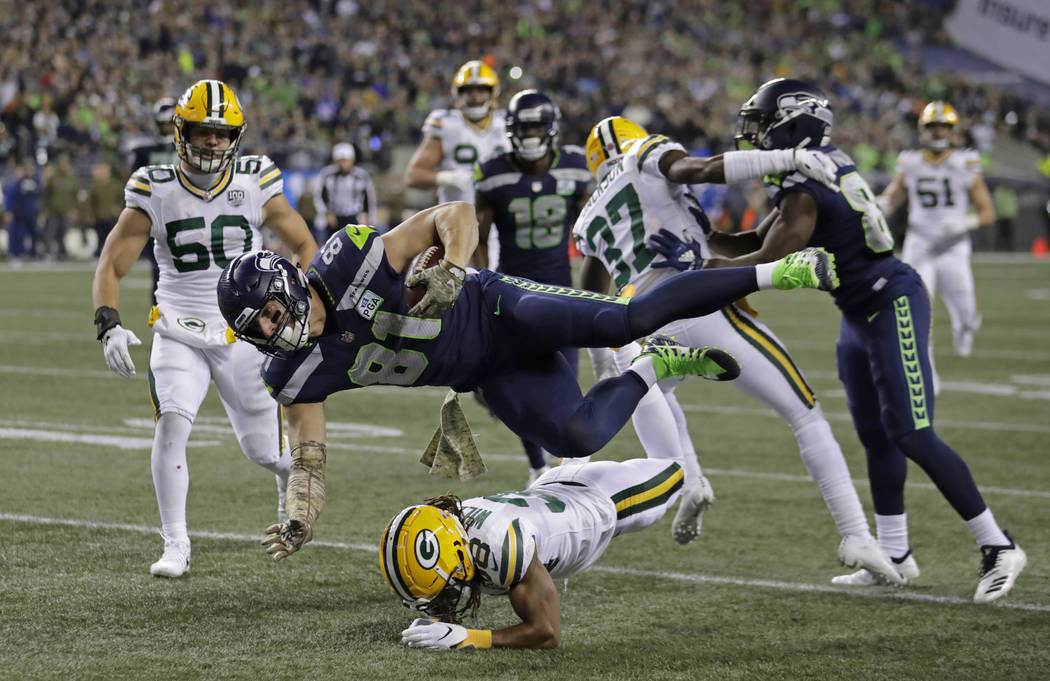 Seattle Seahawks tight end Nick Vannett (81) gets horizontal above Green Bay Packers cornerback Tramon Williams, lower-center, as Vannett carries the ball just short of the goal line against the G ...