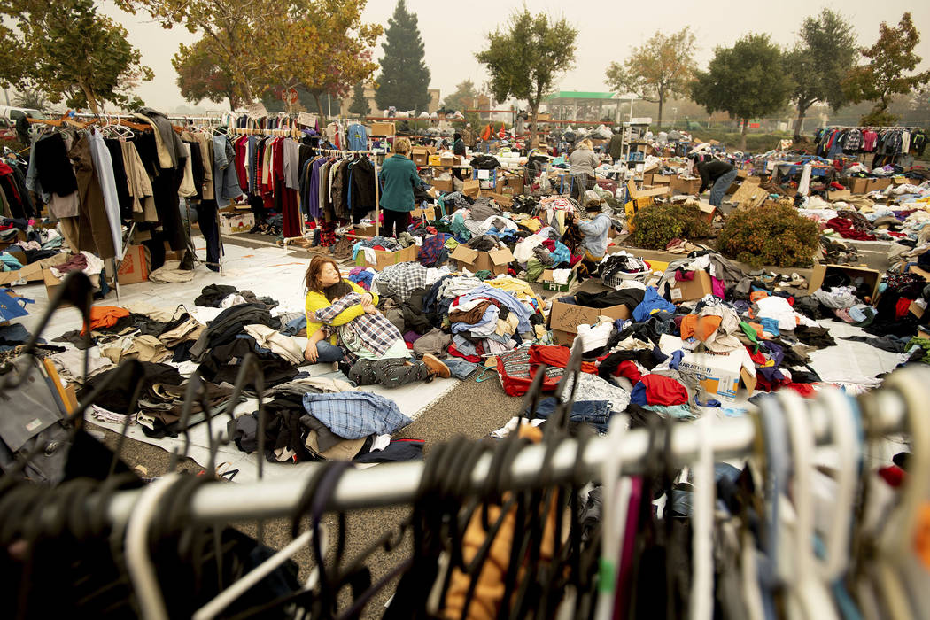 Denise Chester, an evacuee of the Camp Fire, hugs her son Antonio Batres as she volunteers sorting clothes at a makeshift shelter in Chico, Calif., on Wednesday, Nov. 14, 2018. Chester, who doesn' ...