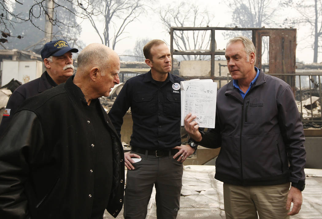 California Gov. Jerry Brown, second from left, looks at a student's workbook, displayed by Interior Secretary Ryan Zinke, that was found during a tour of the fire-ravaged Paradise Elementary Schoo ...