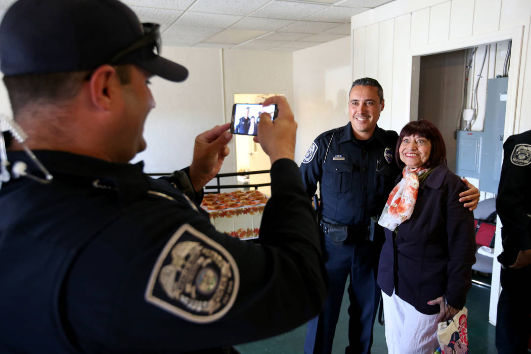 North Las Vegas Police officer Aaron Larotonda takes a photo of fellow officer Aaron Patty with Chantelle Stotler during an early Thanksgiving feast at Rose Gardens senior public housing complex i ...