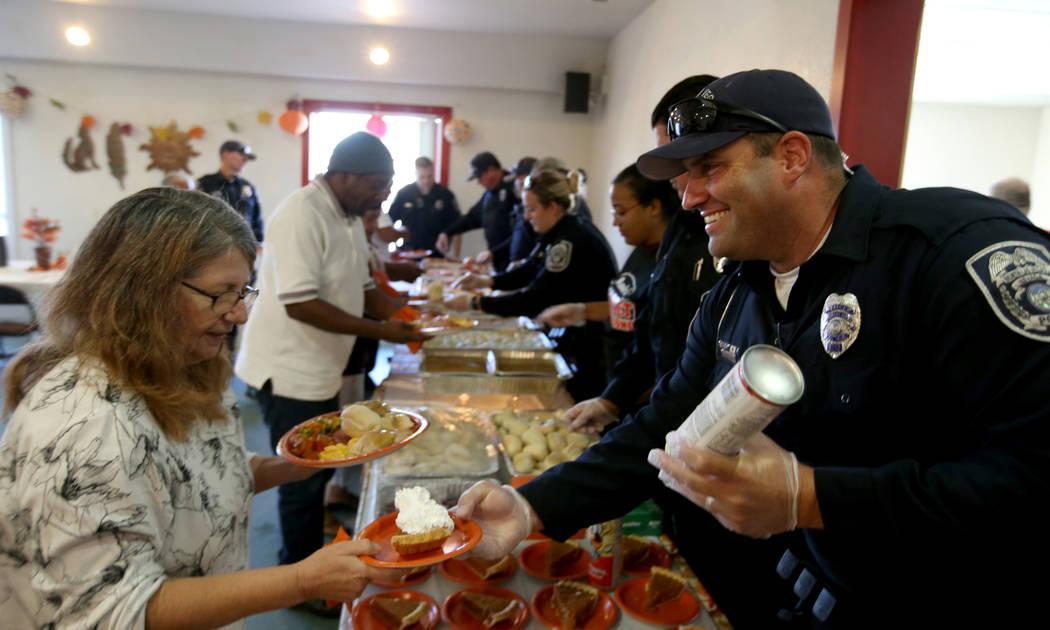 North Las Vegas Police officer Aaron Larotonda serves Ellen Harris, 61, during an early Thanksgiving feast at Rose Gardens senior public housing complex in North Las Vegas Wednesday, Nov. 14, 2018 ...