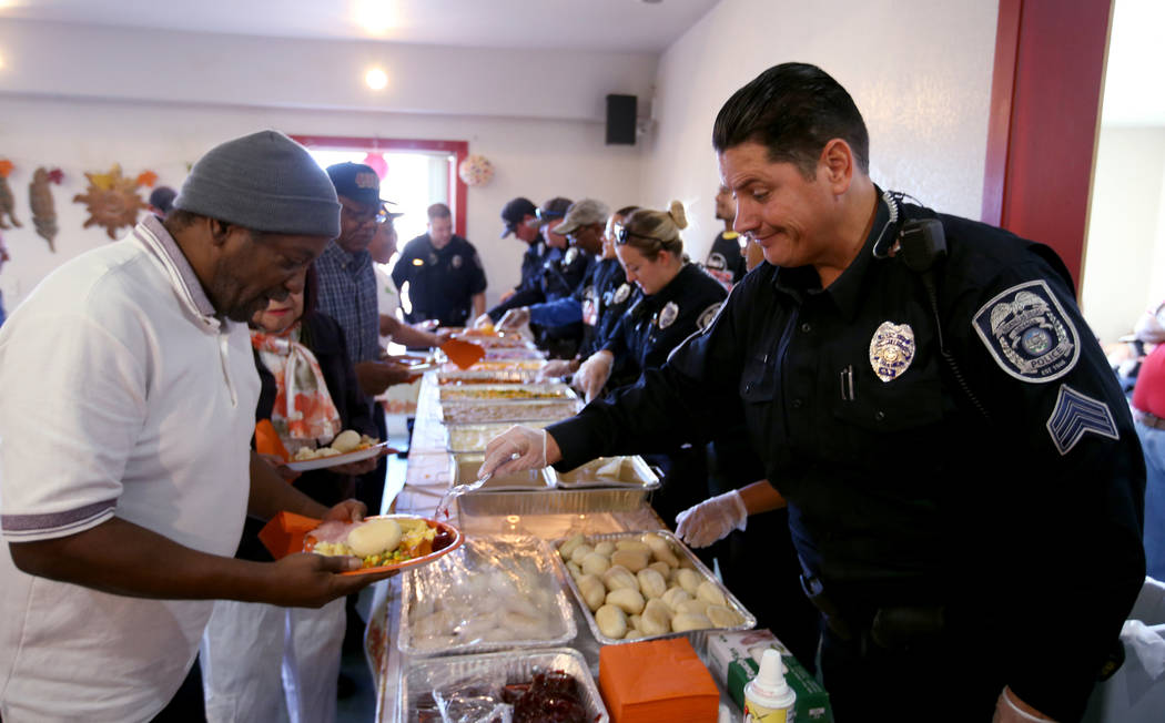 North Las Vegas Police Sgt. Jake Hickman serves Anthony Stubbs, 63, during an early Thanksgiving feast at Rose Gardens senior public housing complex in North Las Vegas Wednesday, Nov. 14, 2018. Ma ...