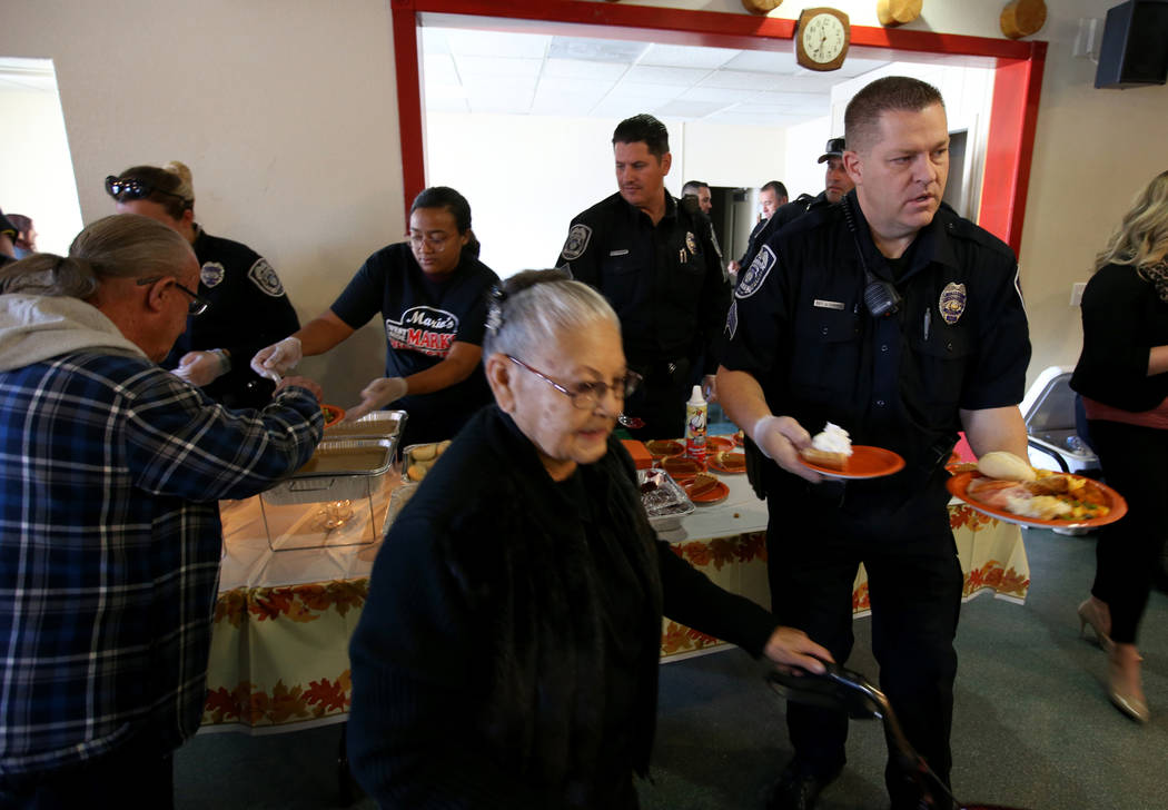 North Las Vegas Police Sgt. John Cargile helps Martha Ramirez, 82, during an early Thanksgiving feast at Rose Gardens senior public housing complex in North Las Vegas Wednesday, Nov. 14, 2018. Mar ...