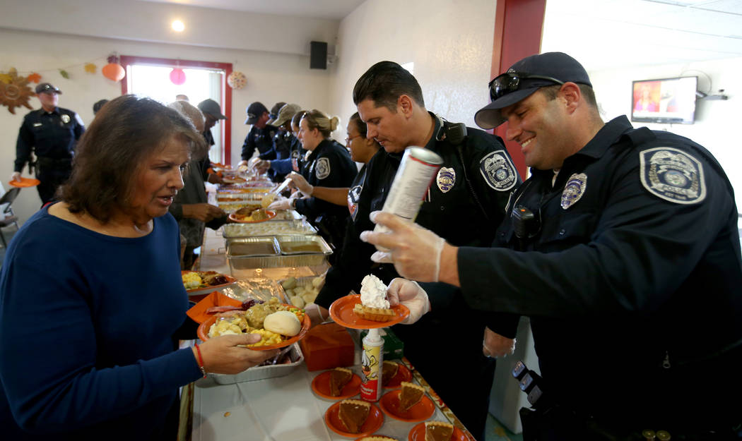 North Las Vegas Police officer Aaron Larotonda serves Frances Reza, 68, during an early Thanksgiving feast at Rose Gardens senior public housing complex in North Las Vegas Wednesday, Nov. 14, 2018 ...
