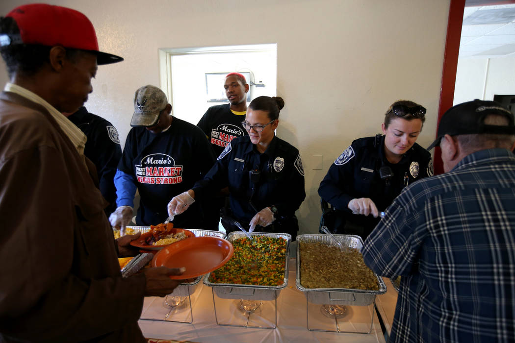 North Las Vegas Police officers C. Ebert, right, and J. Mangual serve Calvin Scott, 60, left, and Richard Roth, 68, during an early Thanksgiving feast at Rose Gardens senior public housing complex ...