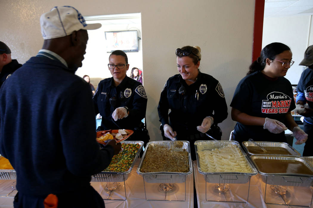 North Las Vegas Police officers J. Mangual, left, and C. Ebert serve Robert Jones, 61, during an early Thanksgiving feast at Rose Gardens senior public housing complex in North Las Vegas Wednesday ...