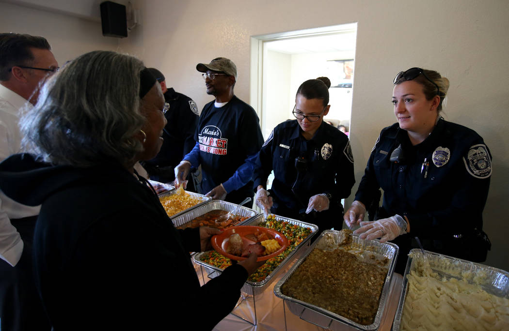 North Las Vegas Police officers C. Ebert, right, and J. Mangual serve Myarm Moore, 61, during an early Thanksgiving feast at Rose Gardens senior public housing complex in North Las Vegas Wednesday ...