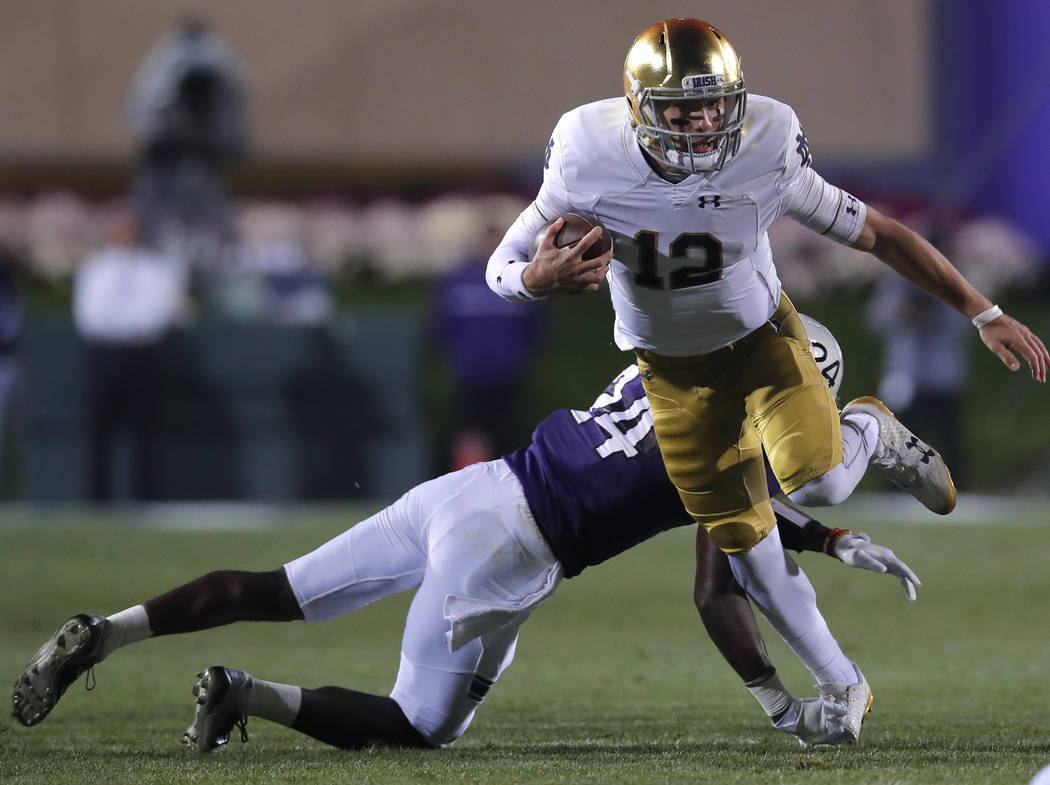 Notre Dame's Ian Book, right, breaks away from a tackle by Northwestern's Montre Hartage during the first half of an NCAA college football game Saturday, Nov. 3, 2018, in Evanston, Ill. (AP Photo/ ...