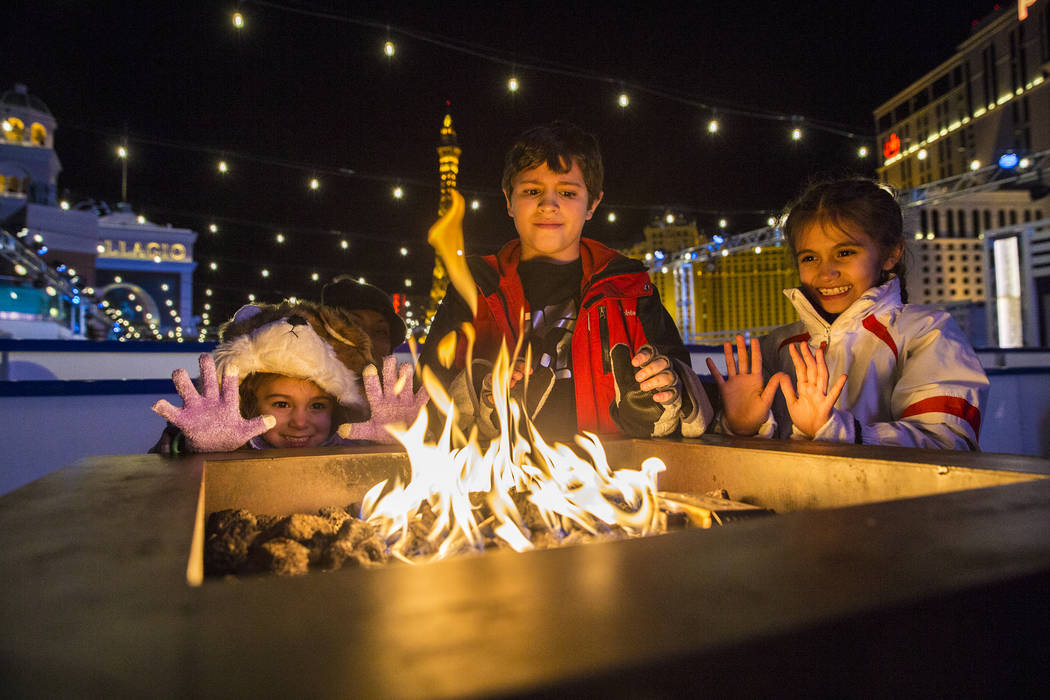 Piper Le Baron, left, stays warm by the fire with siblings Caleb and Reese Le Baron at The Cosmopolitan of Las Vegas Ice Rink on Tuesday, Dec. 20, 2016, in Las Vegas. Benjamin Hager/Las Vegas Revi ...