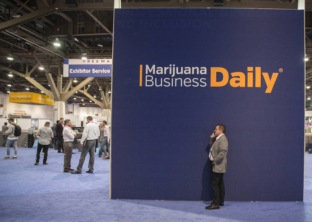 Jaques Santucci, right, with Strimo LP, takes a call in front of signage for the Marijuana Business Daily during the MJBizCon on Wednesday, November 14, 2018, at the Las Vegas Convention Center, i ...
