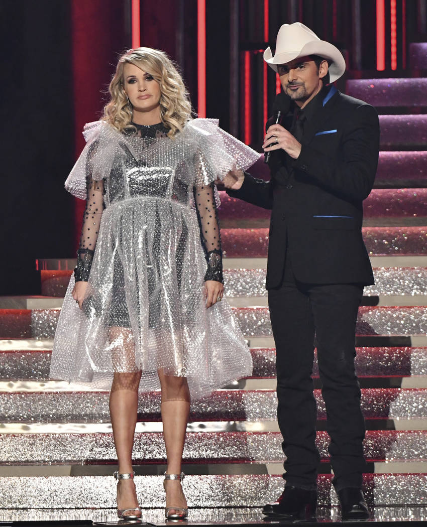 Hosts Carrie Underwood, left, wearing a bubblewrap dress, and Brad Paisley appear at the 52nd annual CMA Awards at Bridgestone Arena on Wednesday, Nov. 14, 2018, in Nashville, Tenn. (Photo by Char ...