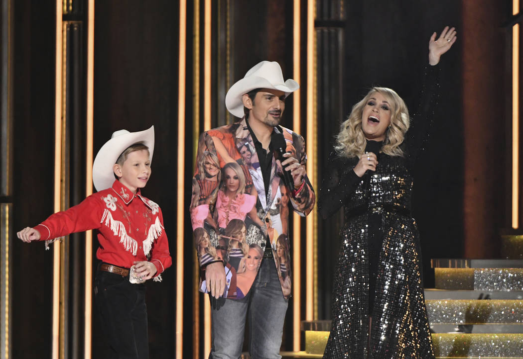 """Mason Ramsey, left, """"Floss"""" dances as hosts Brad Paisley, center, and Carrie Underwood look on at the 52nd annual CMA Awards at Bridgestone Arena on Wednesday, Nov. 14, 2018, in Nashvill ..."""