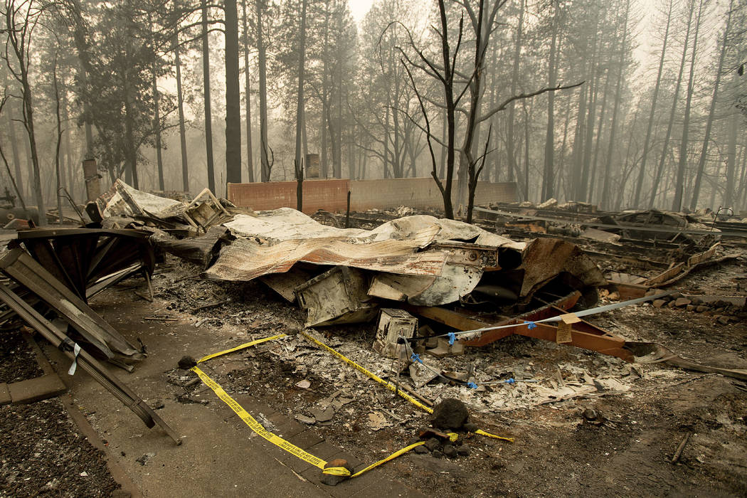 Tape marks a spot where sheriff's deputies recovered the body of a Camp Fire victim on Wednesday, Nov. 14, 2018, in Paradise, Calif. Thousands of homes were destroyed when flames hit Paradise, a f ...