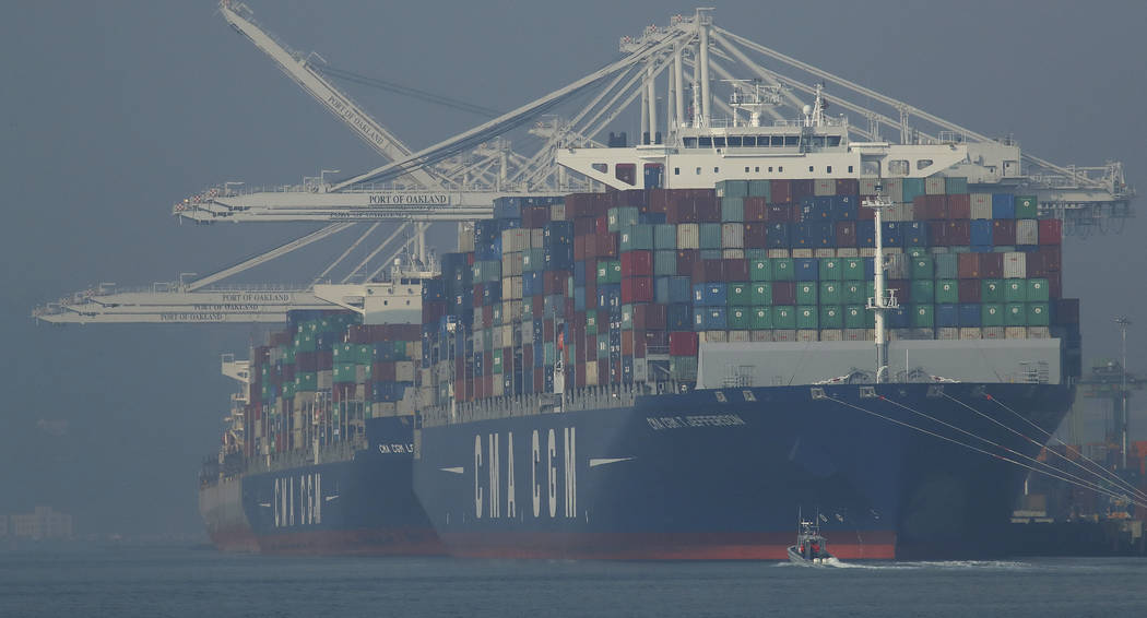 Container ships waiting to be unloaded are seen through a thick haze at the Port of Oakland on Wednesday, Nov. 14, 2018, in Oakland, Calif. Authorities have again issued an unhealthy air quality a ...
