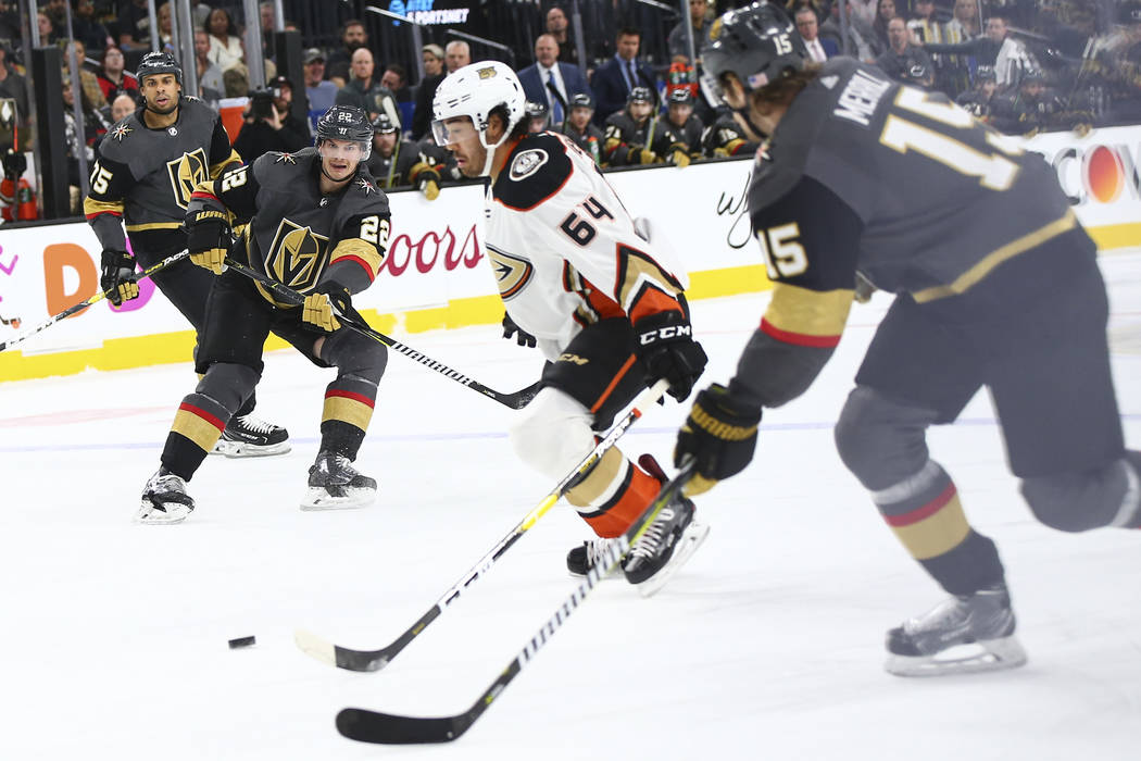 Golden Knights defenseman Nick Holden (22) passes the puck to Golden Knights defenseman Jon Merrill (15) in front of Anaheim Ducks right wing Kiefer Sherwood (64) during the first period of an NHL ...