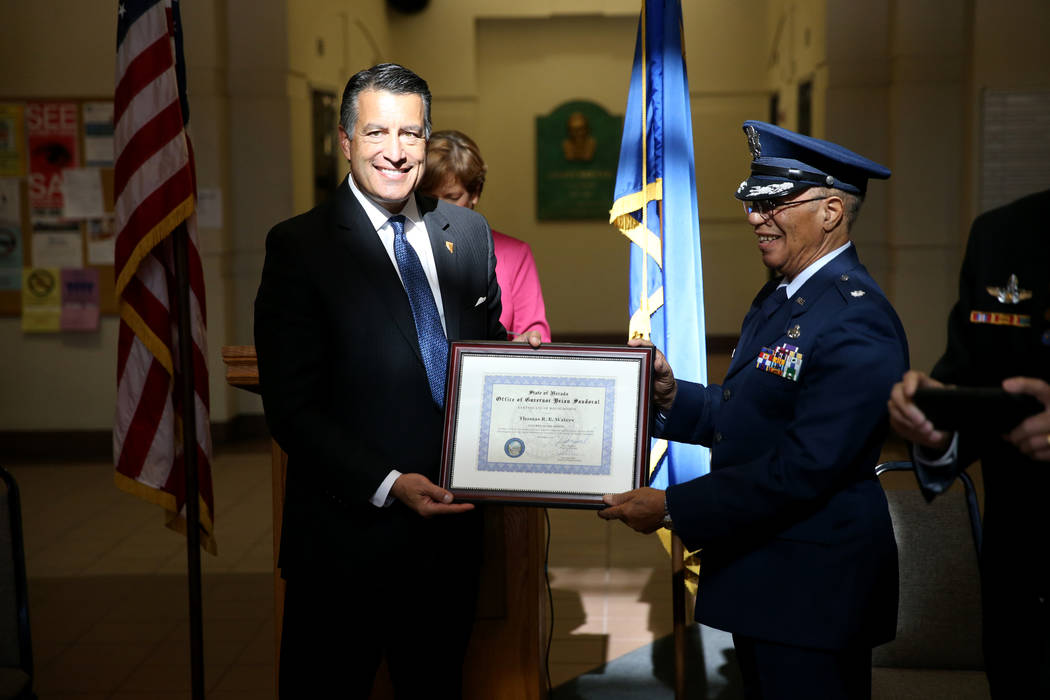 Gov. Brian Sandoval presents Thomas Waters of Pahrump as Nevada Veteran of the Month during a ceremony at the Sawyer Building in Las Vegas Thursday, Nov. 15, 2018. Sandoval also recognized Charm M ...