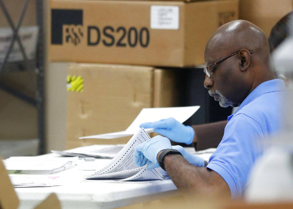 An employee at the Broward County Supervisor of Elections office examines ballots during a recount, Wednesday, Nov. 14, 2018, in Lauderhill, Fla. (AP Photo/Wilfredo Lee)