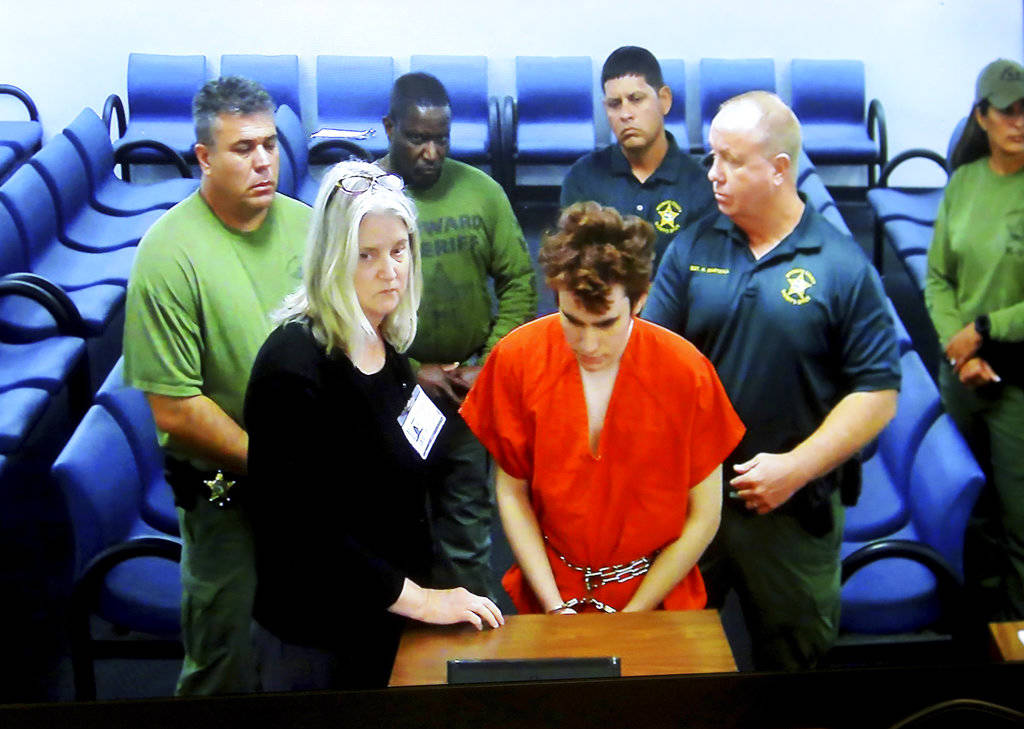 Florida school shooting suspect Nikolas Cruz appears in court via video with public defender Diane Cuddihy in Fort Lauderdale, Fla., Wednesday, Nov. 14, 2018. Cruz attacked a detention officer at ...