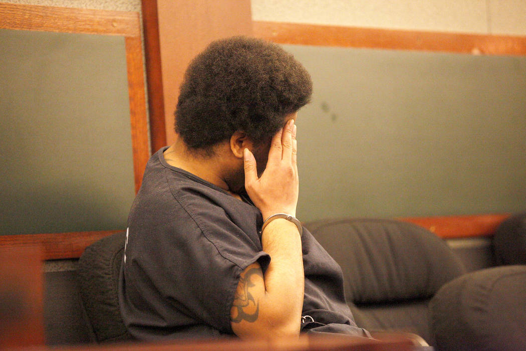 Julius Trotter covers his face in court at the Regional Justice Center in Las Vegas, Thursday, Nov. 15, 2018. Prosecutors announced that they intend to seek the death penalty against Trotter who i ...