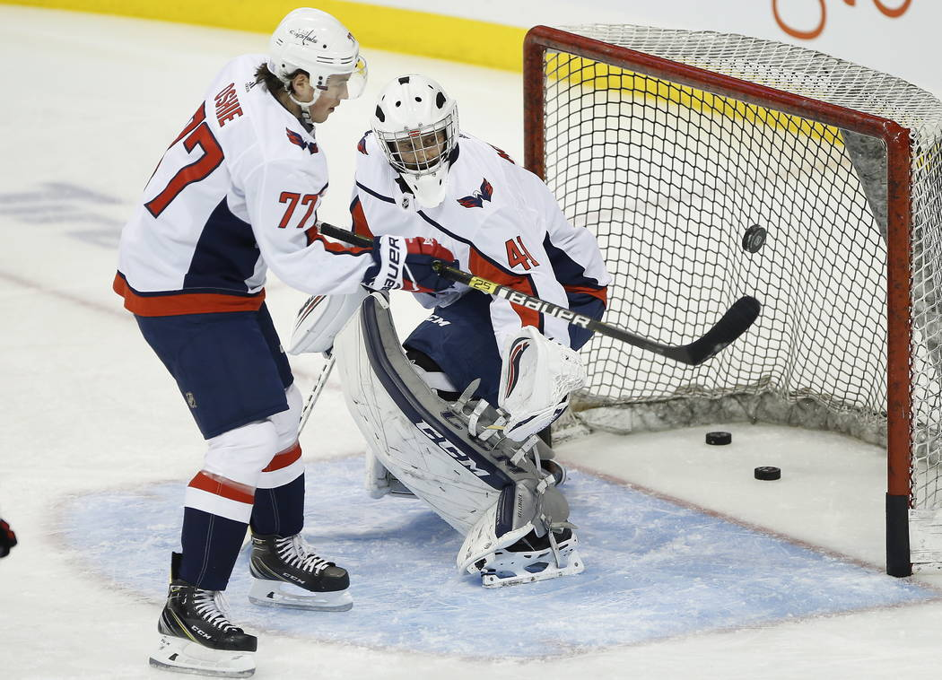 Washington Capitals' T.J. Oshie (77) scores on his goaltender Gavin McHale (41) during the warm up period prior to NHL hockey action against the Winnipeg Jets in Winnipeg, Manitoba on Wednesday, N ...
