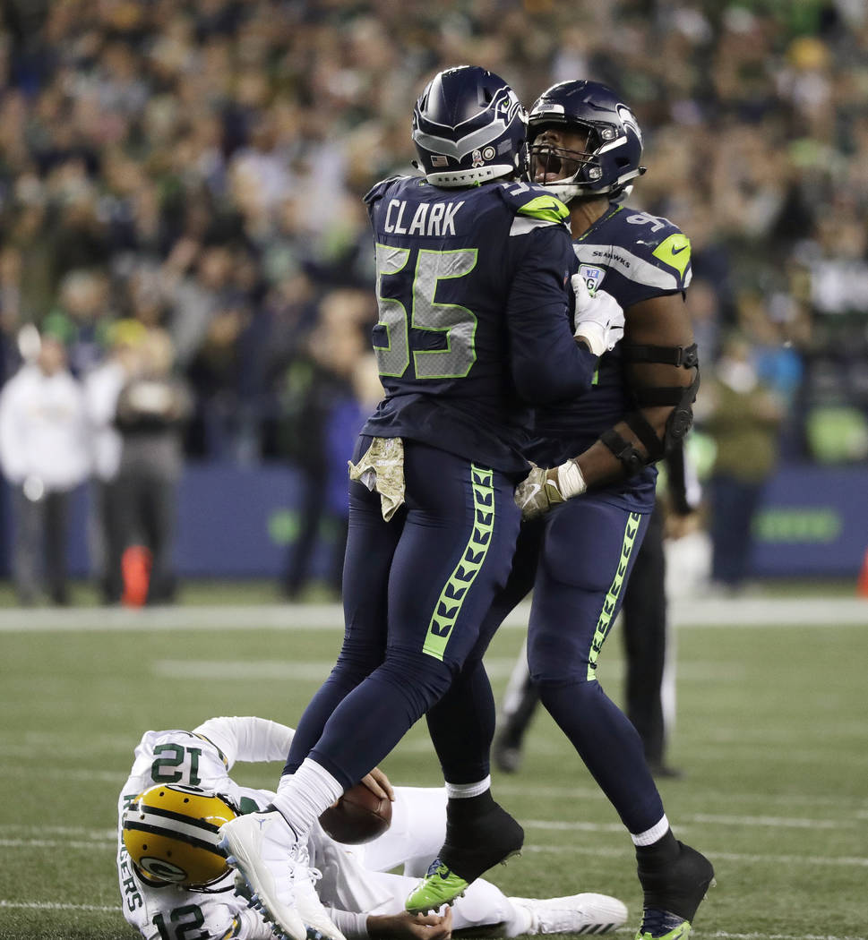 Seattle Seahawks defensive end Rasheem Green, right, celebrates with defensive end Frank Clark (55) after Green sacked Green Bay Packers quarterback Aaron Rodgers, lower left, during the second ha ...