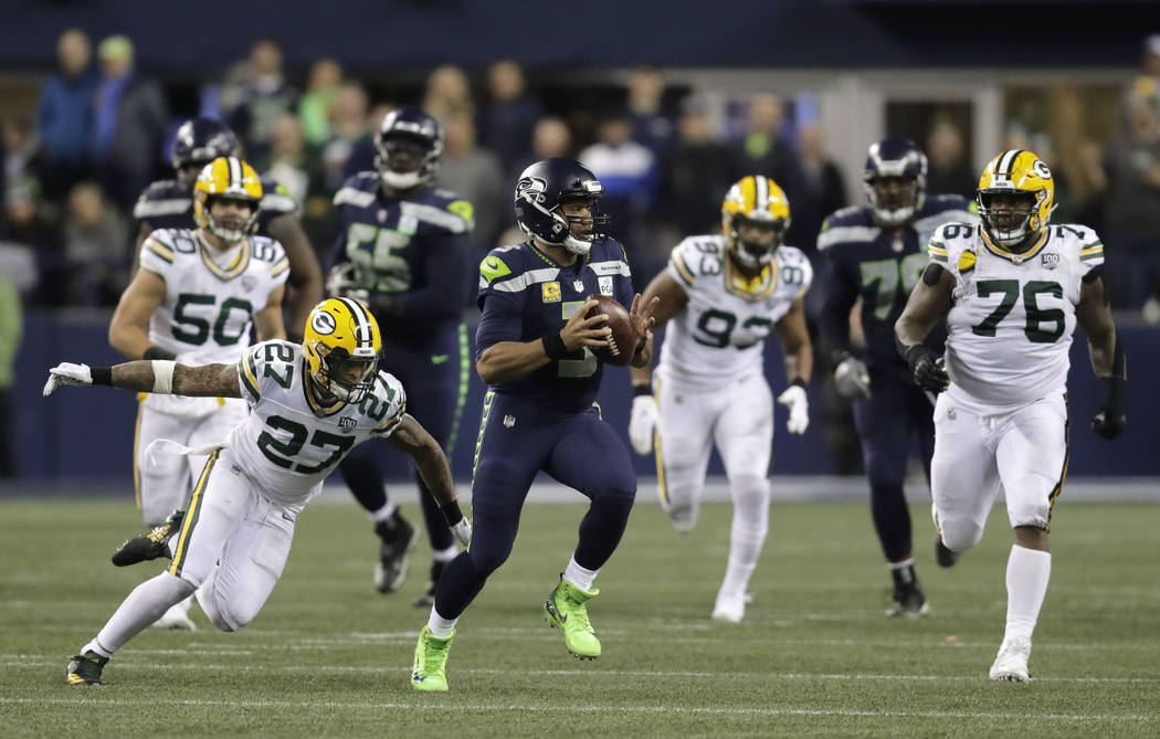 Seattle Seahawks quarterback Russell Wilson (3) scrambles away from Green Bay Packers defensive back Josh Jones (27) during the first half of an NFL football game Thursday, Nov. 15, 2018, in Seatt ...