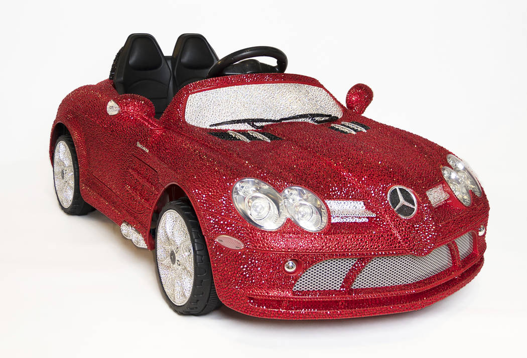 This image released by FAO Schwarz shows a ride-on Mercedes-Benz adorned with more than 44,000 Swarovski crystals in glittery red, white and black for $25,000. (FAO Schwarz via AP)
