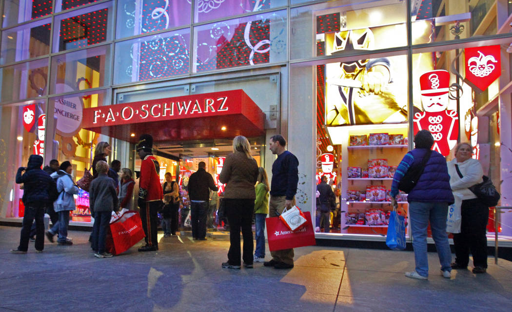 FILE -In this Monday, Nov. 21, 2011 file photo, shoppers pause outside of the Fifth Avenue FAO Schwarz in New York. A new FAO opens Friday, Nov. 16, 2018, in Manhattan's Rockefeller Center, ...