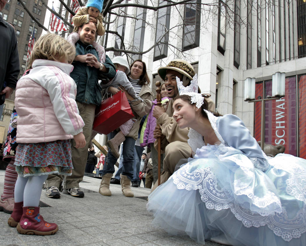 FILE - In this Nov. 22, 2004 file photo, children are greeted by characters from FAO Schwarz outside the store on New York's Fifth Avenue. Three years after it closed its beloved toy store on Fift ...