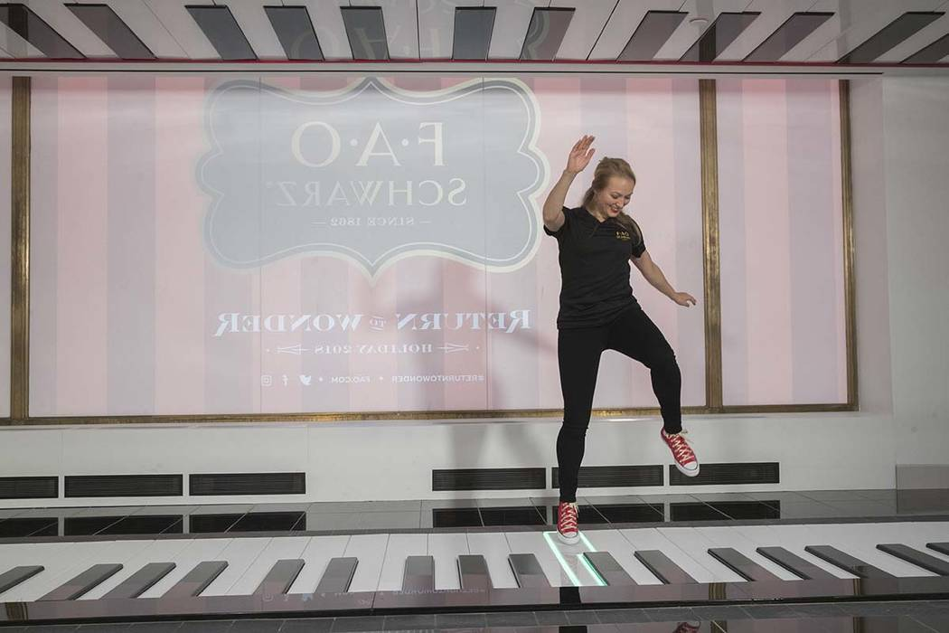 In this Tuesday, Nov. 13, 2018 photo, an employee plays the FAO Premium Piano Dance Mat during a media preview of the new FAO Schwarz store at Rockefeller Center in New York. (AP Photo/Mary Altaffer)