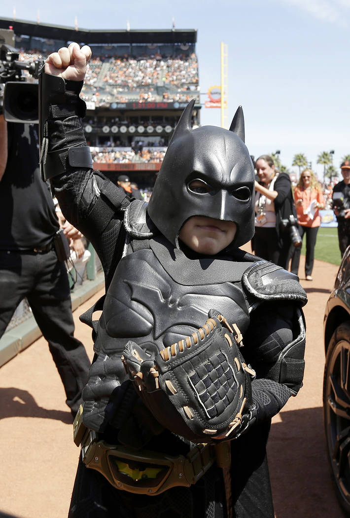In this file photo from Tuesday, April 8, 2014, Miles Scott, dressed as Batkid, gestures after throwing the ceremonial first pitch before a baseball game between the San Francisco Giants and the A ...