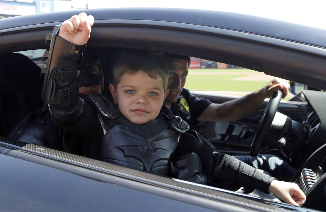 In this file photo from Tuesday, April 8, 2014, Miles Scott, dressed as Batkid, gestures as he sits in the Batmobile after throwing the ceremonial first pitch before a baseball game between the Sa ...