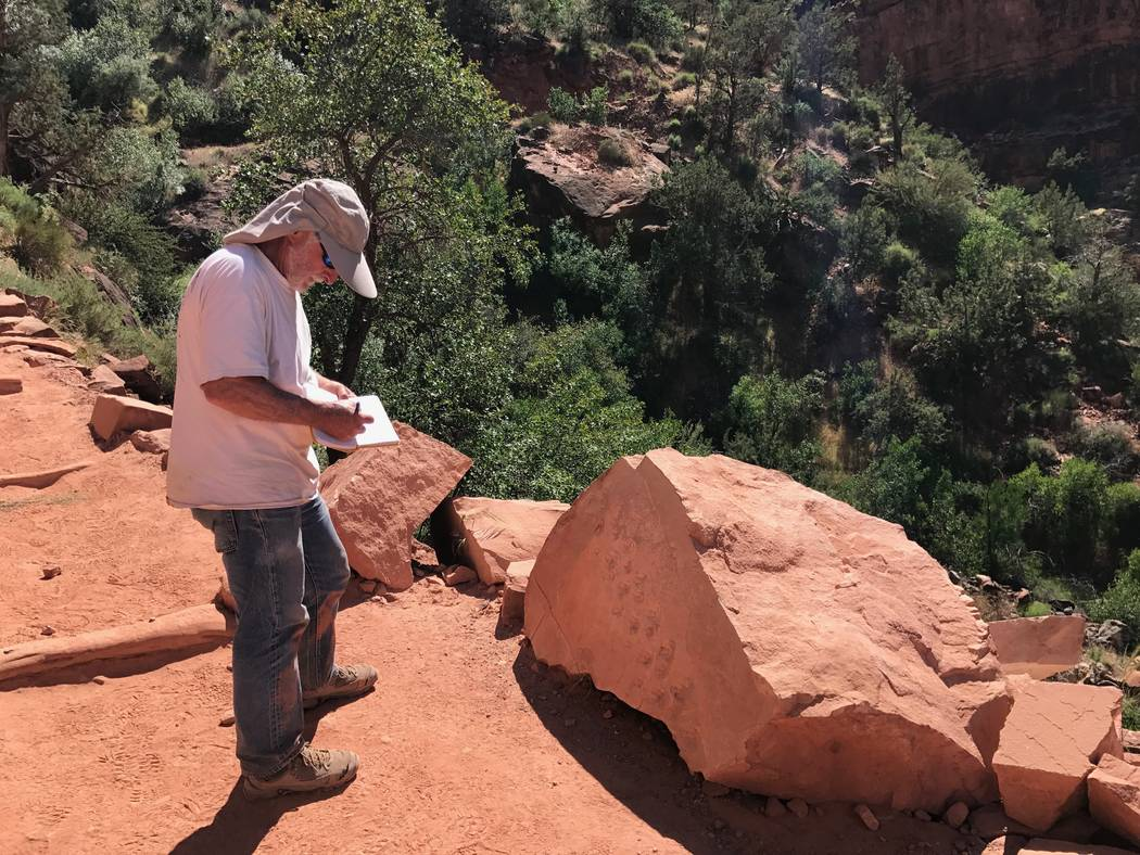 UNLV geologist Steve Rowland sketches fossilized footprints on a rock along the Bright Angel Trail at Grand Canyon National Park in this undated photo. Eric Rowland