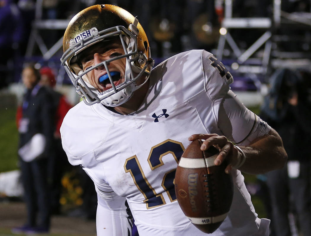 FILE - In this Saturday, Nov. 3, 2018, file photo, Notre Dame's Ian Book celebrates as he scores a touchdown against Northwestern during the second half of an NCAA college football game in Evansto ...