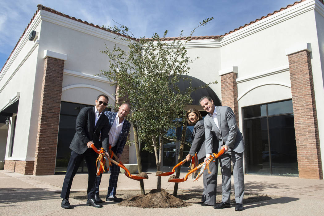 Mike Nigro, new owner, left, Michael Young, senior associate, Henderson Mayor Pro Tem Gerri Schroder and Mike Nigro, new owner, pose for a photograph outside of one of the newly purchased building ...