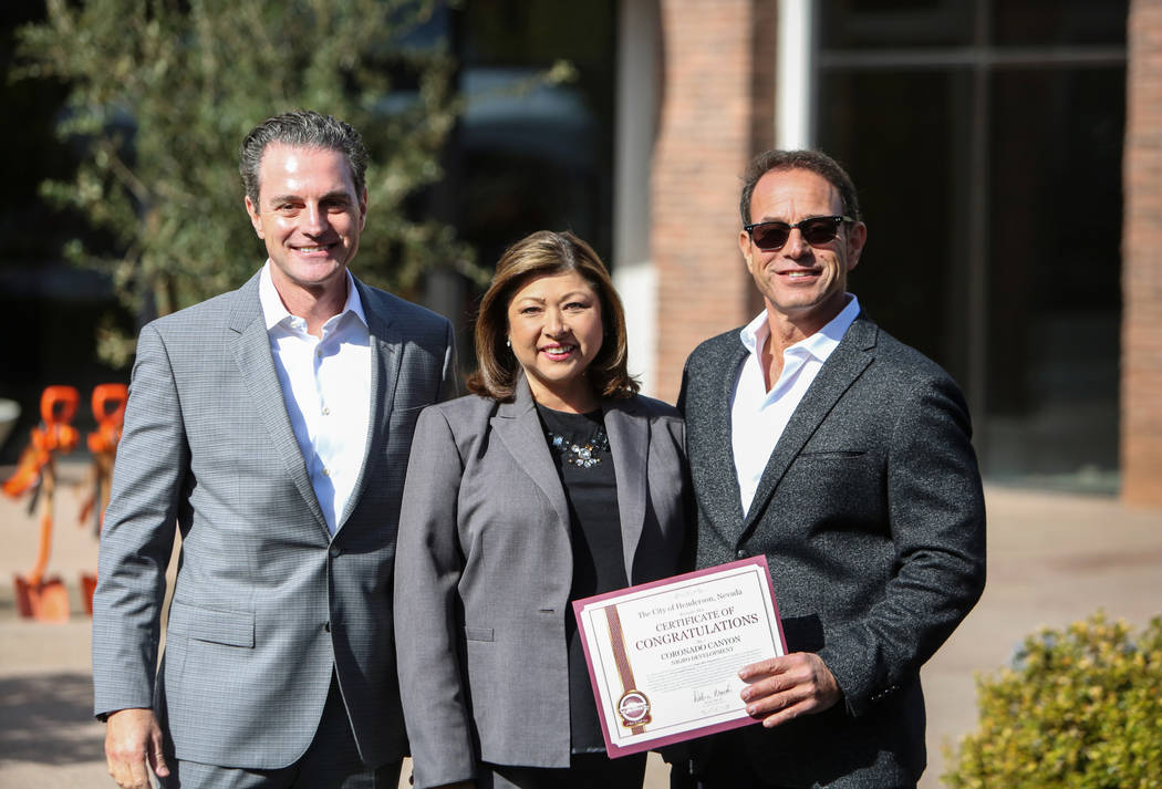 Mike Nigro, new owner, left, Henderson Mayor Pro Tem Gerri Schroder and Mike Nigro, new owner, pose for a photograph outside of one of the newly purchased buildings during a ceremony to held to ma ...