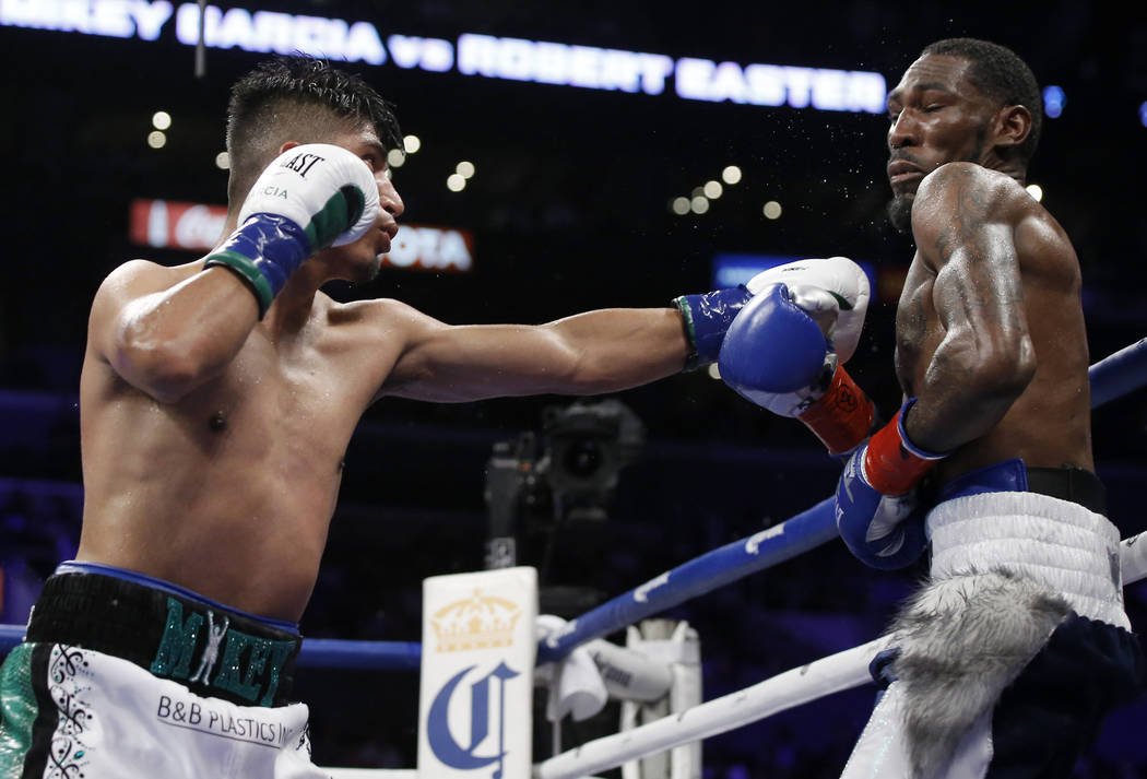 Mikey Garcia, left, hits Robert Easter Jr. with a left during the tenth round of their WBC and IBF lightweight title bout in Los Angeles, Saturday, July 28, 2018. Garcia won by unanimous decision. ...