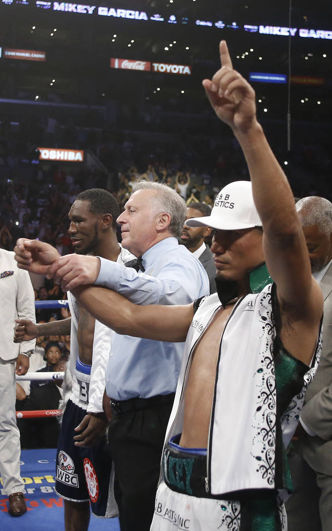 Judge Jack Reiss, center, raises Mikey Garcia's, right, arm to announce Garcia's unanimous decision win over Robert Easter Jr., left, in their WBC and IBF lightweight title bout in Los Angeles, S ...