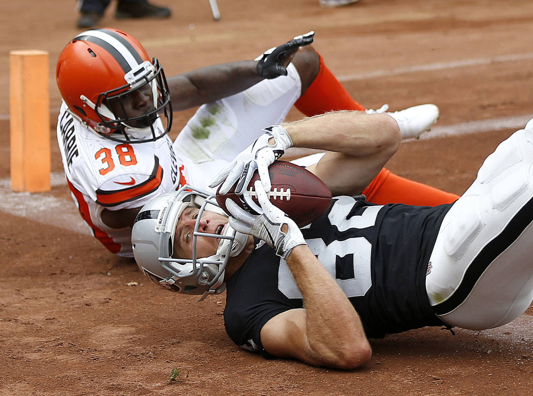 Oakland Raiders wide receiver Jordy Nelson, bottom, converts a two point conversion in front of Cleveland Browns defensive back T.J. Carrie (38) during the second half of an NFL football game in O ...
