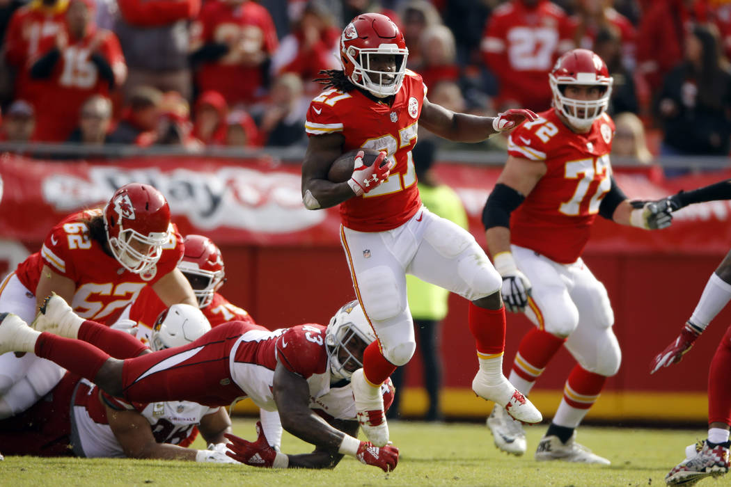 Kansas City Chiefs running back Kareem Hunt (27) runs away from a tackle-attempt by Arizona Cardinals linebacker Haason Reddick (43) during the first half of an NFL football game in Kansas City, M ...