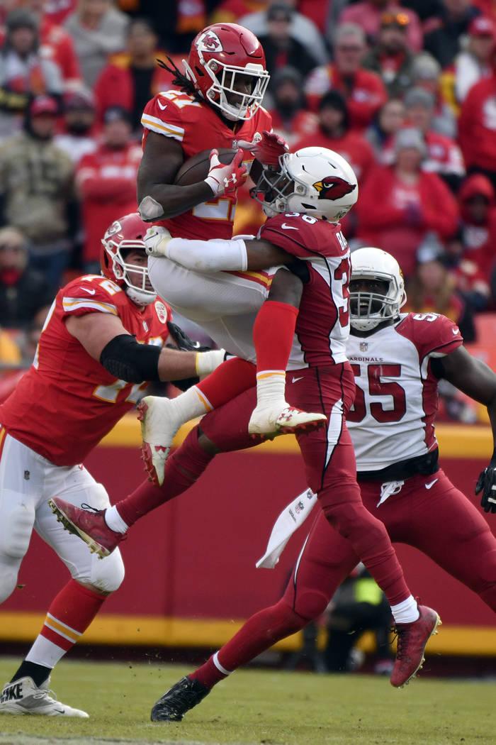 Kansas City Chiefs running back Kareem Hunt (27) attempts to vault Arizona Cardinals safety Budda Baker (36) during the second half of an NFL football game in Kansas City, Mo., Sunday, Nov. 11, 20 ...