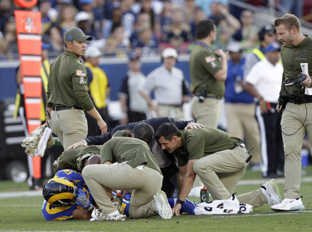 Los Angeles Rams head coach Sean McVay, right, checks up on the injured wide receiver Cooper Kupp, left, while being attended to by the medical staff during the second half in an NFL football game ...
