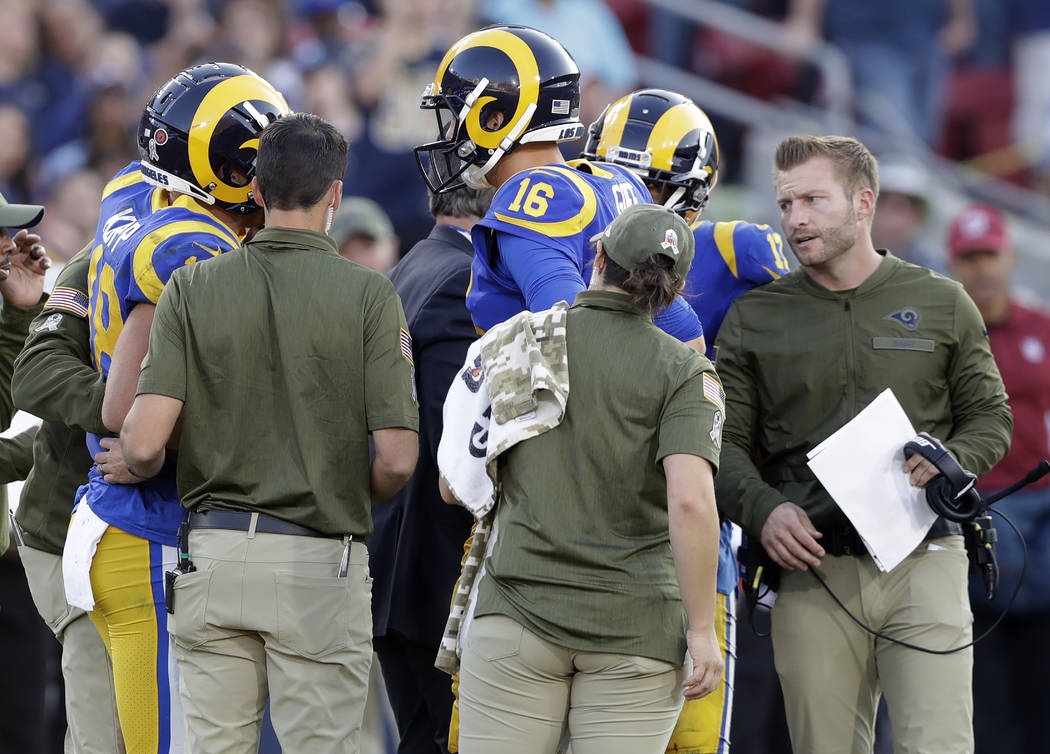 Los Angeles Rams head coach Sean McVay, right, and quarterback Jared Goff (16) check up on the injured wide receiver Cooper Kupp, left, while he is being attended to by the medical staff during th ...